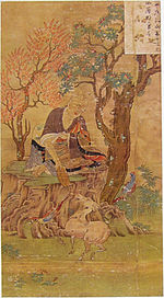 A priest seated under a tree feeding a four-legged animal in the shape of a small horse.