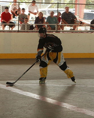 Roller in-line hockey - A collegiate inline hockey player carrying the puck.