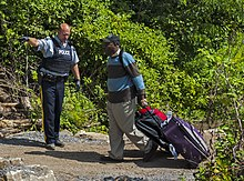 "A bald uniformed police officer wearing black gloves and a blue flack jacket with ""POLICE"" written on it in white letters at left points in that direction while a man on the right in a blue and brown striped sweater wearing a baseball cap pulls a wheeled suitcase behind him on a dirt pathway with shrubs behind him"
