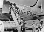 Australian soldiers deplane a Qantas Empire Airways Douglas DC-4 (VH-EBK).jpg
