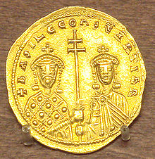 A photograph of a gold coin depicting two crowned figures, both grasping a double-barred patriarchal cross between them