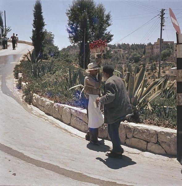 File:Bedelaar en een verkoper van lollies langs de kant van een weg bij een laag muur, Bestanddeelnr 255-9347.jpg
