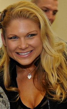 A blond woman smiles while wearing a black top, a silver necklace and a brooch in her hair.