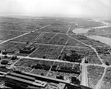 Black and white aerial photo of an urban area comprising several large buildings separated by large fields of rubble. Streets and rivers are visible.