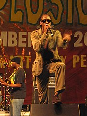 Man with cornrows singing into microphone onstage