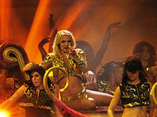 Image of a blond female performer surrounded by a group of dancers. She is sitting on a purple coach and wearing a golden outfit. The dancers are wearing short black hooded sweatshirts.