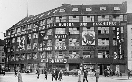 "Karl-Liebknecht-Haus, the KPD's headquarters from 1926 to 1933. The Antifaschistische Aktion (a.k.a. ""Antifa"") logo can be seen prominently displayed on the front of the building. The KPD leaders were arrested by the Gestapo in this building in January 1933, when Hitler became Chancellor. The plaques on either side of the door recall the building's history. Today it is the Berlin headquarters of the Left Party. Bundesarchiv B 145 Bild-P046279, Berlin, Liebknecht-Haus am Bulowplatz.jpg"