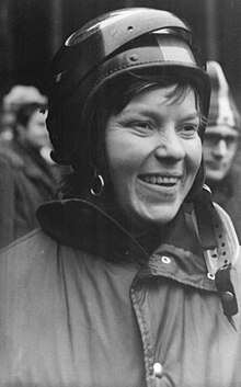 A smiling brunette woman wearing a winter jacket and a full-face helmet with a lifted visor.