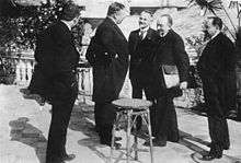 Five men stand around a table.