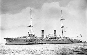 A large warship with several guns and two tall masts at anchor