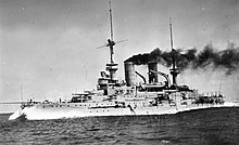 A large, light gray battleship plows through the water at high speed. Thick black smoke pours from the two round smoke stacks