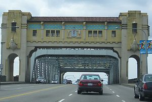 Burrard Bridge - East (city) pylon with decorations, masking steel through-truss; six traffic lanes, pedestrian arches, concrete railings