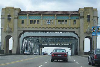 Burrard Bridge - East (city) pylon with decorations, masking steel through-truss; six traffic lanes, pedestrian arches, concrete railings