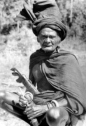 Sumba people - A Ratu Merapu (Marapu ritual specialist) in a traditional attire, complete with a Kabeala is seen preparing his sirih pipe, 1943.