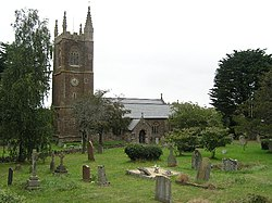 Stone building with square tower. In the foreground are gravestones and trees.