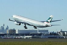 White jet passenger aircraft with thick green cheatline taking off from runway.