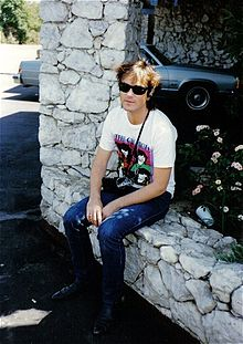 Steve Kilbey is sitting on a low rock wall beside a garden bed and a rock pillar. He is wearing dark glasses, a white tee-shirt with The Church and four faces (partly obscured), and jeans.