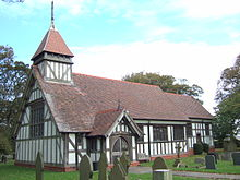 A small black and white half-timbered church showing the nave with a porch, a small chancel beyond and a small spire on the nearside of the roof; some gravestones visible in the churchyard.