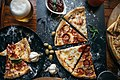 Close-up of classic italian Pizza on a old rustic wooden table with beer in glass cups (49134020743).jpg