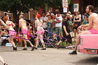 Suspension (body modification) - Topless men and women pulling a car using ropes attached to flesh hooks inserted in their backs. The participants are not suspended from top in this case. Scene from Doo Dah Parade, Ohio, USA, 2011.