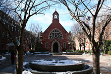 A frontal view of the red, brick edifice of the chapel. In front is a brick quadrangle with some snow on the ground, all centered between two trees in the foreground.