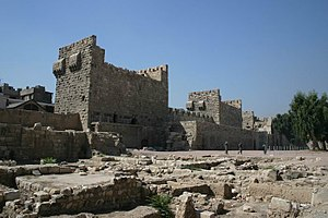 A stone wall intersected by three square towers with the ruins of another building in the foreground