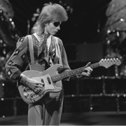 A black and white photo Bowie with longer hair and an eyepatch, holding a guitar and looking down at it