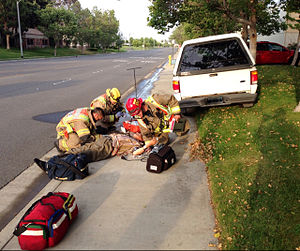 Diabetes management - Paramedics in Southern California attend a diabetic man who lost effective control of his vehicle due to low blood sugar (hypoglycemia) and drove it over the curb and into the water main and backflow valve in front of this industrial building. He was not injured, but required emergency intravenous glucose.