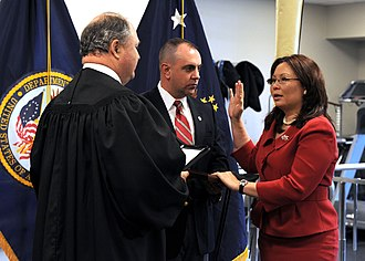 Tammy Duckworth - Duckworth being sworn in as Assistant Secretary of Public and Intergovernmental Affairs for the United States Department of Veterans Affairs, by Judge John J. Farley with her husband Bryan Bowlsbey beside her.