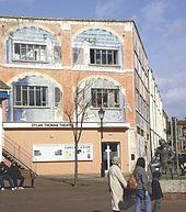 Uma ampla três edifício andares com janelas para a parte superior duas histórias e uma entrada no piso térreo.  Uma estátua de Thomas fica fora.