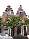foto van Huis met trapgevel, toppilaster op een maskerkraagsteen.Tweelichtzoldervensters, met een luik van geprofileerde planken. Trapgevel gekoppeld met die van buurnummer 7