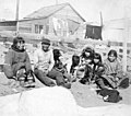 Eskimo family sitting on beach near buildings and tents, Nome, Alaska, between 1908 and 1915 (AL+CA 6444).jpg