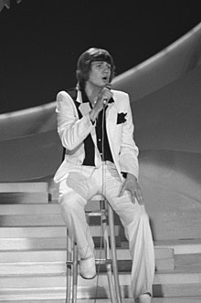Black and white photograph of Johnny Logan performing on stage at the 1980 contest