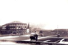 Uma fotografia que mostra trabalhadores espalhar ou recolhendo grãos de café que secam em uma grande praça pavimentada com um elegante edifício de dois andares neoclássico à esquerda e armazéns e outros edifícios de plantação em segundo plano