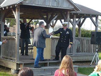 Ferndale, California - Lt. Jeremy M. Schwartz hands the keys of surplus U.S. Navy Housing to Ferndale Mayor Jeff Farley at the Navy Housing Picnic Shelter in Ferndale, California, on October 23, 2011.