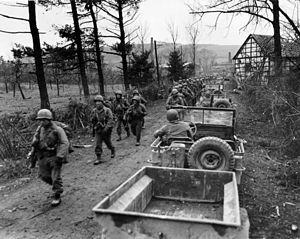 18th Infantry Regiment (United States) - Company C, 1st Battalion, 18th Infantry Regiment, 1st Infantry Division moving up into Frauwüllesheim, Germany, after crossing the Roer River on 29 February 1945.