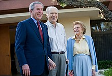 A man in a suit is standing next to an older man and woman in casual attire. The trio stands in front of a yellow house.