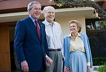 Um homem em um terno está de pé ao lado de um homem mais velho e uma mulher em traje casual.  O trio está na frente de uma casa amarela.