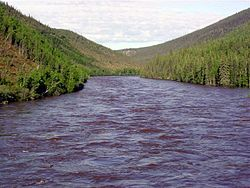 A choppy river is seen surrounded by tree-covered hills.