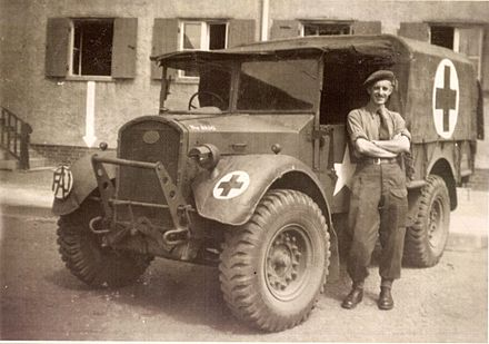 FAU ambulance and driver, Germany, 1945 Friends Ambulance Unit ambulance driver, with his vehicle in Wolfsburg, Germany.jpg