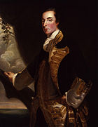 A three quarter length portrait of Admiral Rodney in relative youth. He stands before a mostly dark background; his right hand rests on what looks like a large tree branch, behind which the sea is visible. He wears a dark coat with gold embroidery over a white waistcoat.