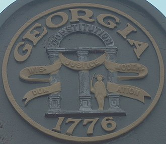 Georgia Historical Commission - Seal of Georgia on.an old historical marker, showing that the Georgia Historical Commission was under the State of Georgia until 1973.