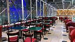 Green tables and red chairs in The Lawn, Paddington Station, London.jpg