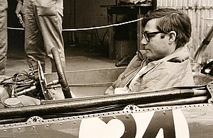 Masten Gregory - Masten Gregory waits in the cockpit of his BRM, at the Nürburgring in 1965 German Grand Prix.