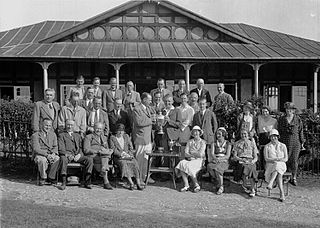 People outside Llandrindod Wells Golf Club pavilion, with a gentleman golfer being presented with a cup