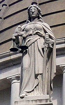 blindfolded lady with sword in right hand held vertically down to floor, and a set of balance scales in her left hand held neck high
