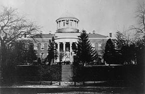 A black-and-white photo of a building situated on a hill and partially obscured by trees. A cupola with a clock sits on the roof.