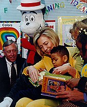 Same woman reads a book in a classroom to an African American boy in her lap, as an African American girl and two adults look on