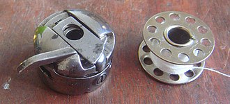 Bobbin - Bobbin (right) and bobbin case for a Chinese-made Hua Nan sewing machine