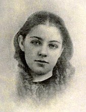 A soft photographic portrait of a girl approximately 11 years old, shown from the neck up, wearing a simple dark garment with no collar, her hair parted in the middle and falling straight to frame her cheeks, turning to ringlets at her neck and shoulders, the head tilted slightly to the right, the eyes looking directly forward. The image shows loss of detail from wear.